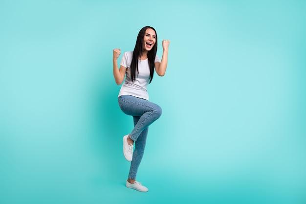 Lichaamsgrootte van volledige lengte draaide foto van vrolijke gekke verheugende extatische vrouw die ja schreeuwde in spijkerbroek denim schreeuwde geïsoleerde levendige blauwgroen achtergrond
