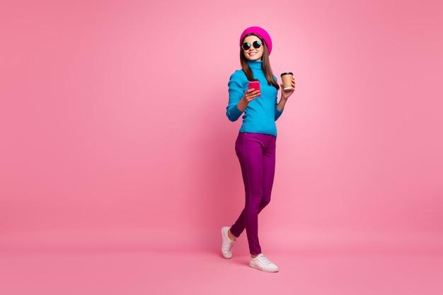 Lichaamsgrootte van volledige lengte van haar, mooi aantrekkelijk mooi mooi slank fit dun vrolijk vrolijk meisje in de hand cel wandelen genieten van het drinken van latte.
