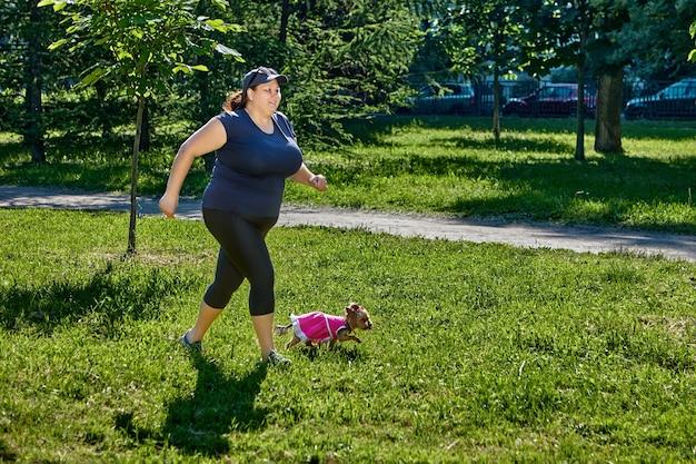 Lichaamspositiviteitsconcept een zwaarlijvige vrouw die in park jogt met haar yorkshire terrier-hond