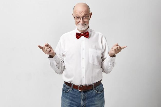 Lichaamstaal. aantrekkelijke zelfverzekerde volwassen zeventigjarige blanke man met spijkerbroek
