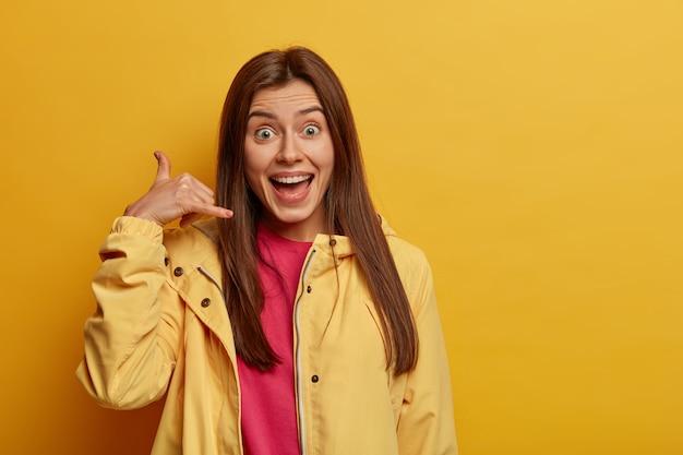 Lichaamstaal concept. positieve brunette vrouw maakt oproepgebaar, zegt bel me terug, draagt een gele anorak, vraagt om nummer, kijkt graag naar de camera