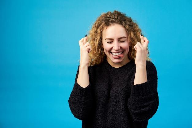Lichaamstaal. emotionele gelukkige jonge aantrekkelijke roodharige krullende vrouw die tong toont en vingers kruist voor geluk.