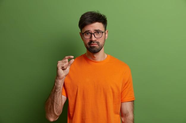 Lichaamstaal en maatconcept. jonge ontevreden man toont kleine maatregel, vertelt over zijn kleine salaris, vormt iets kleins, oordeelt slechte kwaliteit, draagt oranje t-shirt, geïsoleerd op groene muur