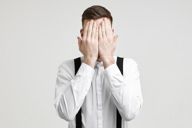 Lichaamstaal en non-verbaal communicatieconcept. geïsoleerd schot van onherkenbaar europees mannetje dat wit formeel overhemd draagt met bretels die het gezicht bedekken met beide handpalmen, zich gestrest en moe voelen