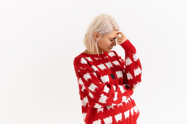 Lichaamstaal. foto van blonde modieuze tienermeisje in trendy pullover naar beneden kijken, hand op haar voorhoofd houden, proberen te concentreren, zich iets herinneren, met peinzende gezichtsuitdrukking
