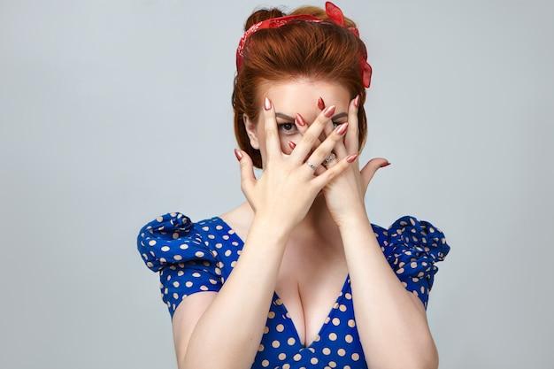 Lichaamstaal. foto van stijlvolle mooie jonge dame in retro kleding poseren in studio die betrekking hebben op gezicht met handen, turen naar camera door vingers, hebben bang