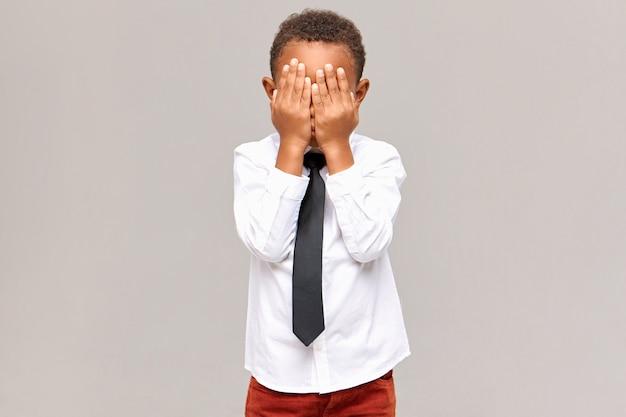 Lichaamstaal. geïsoleerd beeld van boos gefrustreerde donkere mannelijke elementaire leerling die de ogen bedekt met beide handen, zijn emoties verbergt, huilend vanwege een slecht cijfer op school