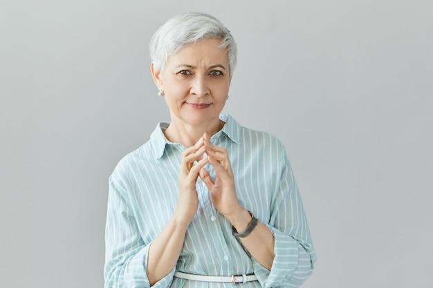 Lichaamstaal. geïsoleerd beeld van succesvolle zelfverzekerde zakenvrouw met korte haarstijl planning hand in hand klapten samen, met doordachte mysterieuze gezichtsuitdrukking