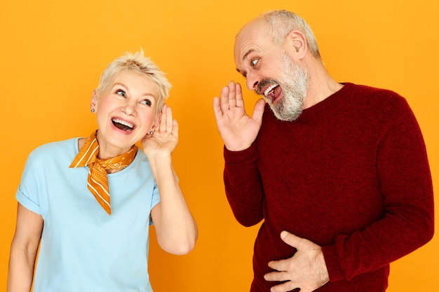 Lichaamstaal. portret van twee grappige bejaarde kaukasische gepensioneerden met gehoorprobleem die gesprek hebben, handen op oor houden en schreeuwen maar kunnen geen woorden onderscheiden. doofheid concept