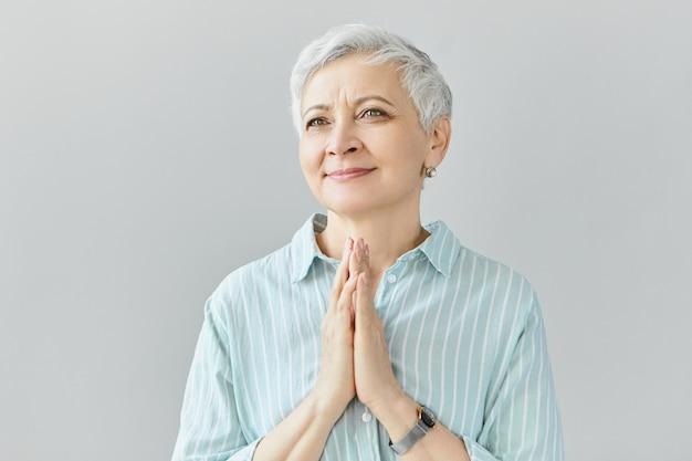 Lichaamstaal. positieve charmante volwassen grootmoeder klappende handen, glimlachend, trots op haar getalenteerde kleinzoon. elegante grijze haren vrouw poseren geïsoleerd met een gelukkige glimlach, aangeraakt blik