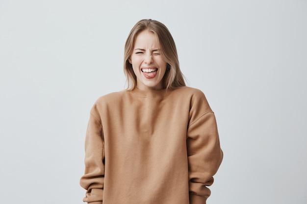 Lichaamstaal. weerzinwekkende gestreste mooie vrouw met steil blond haar poseert, fronst haar gezicht, sluit ogen en steekt haar tong uit, wat een afkeer van iets toont