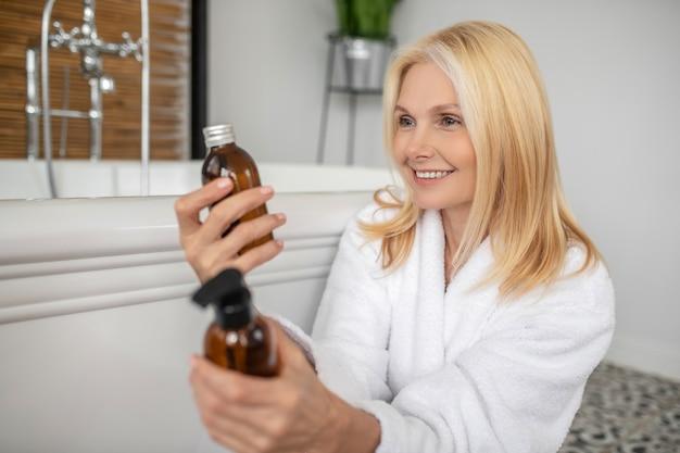 Lichaamsverzorging. blonde leuke vrouw die de producten van de lichaamsverzorging kiest