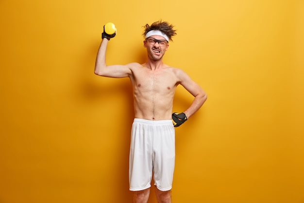 Lichaamsverzorging en training concept. ontevreden europese man houdt sportuitrusting omhoog, tilt dummbell met kracht op, gekleed in korte broek en handschoenen, spant zich in om het doel te bereiken, leidt een actieve levensstijl