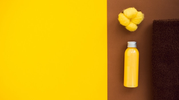 Lichaamsverzorging plat leggen met plantkatoen, handdoek, douchegel of body cream. gele en bruine kleur, kopie ruimte