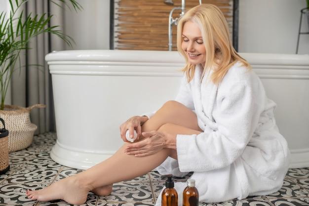 Lichaamsverzorging. schattige blonde vrouw zittend op de vloer in een badkamer en crème op haar benen toe te passen