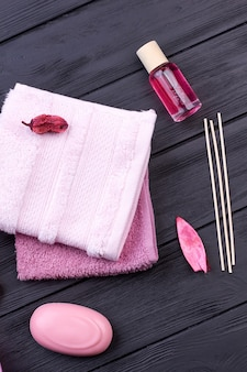 Lichaamsverzorging spa spullen op donker houten bureau. badstof handdoek met zeep en fleslotion.