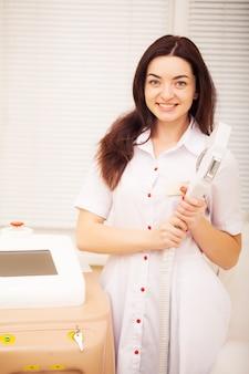 Lichaamsverzorging. vrouw arts die machine voor de verwijdering van het laserhaar toont