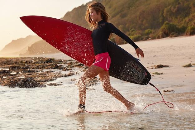 Lichamelijke activiteit en verbinding met de natuur. positieve surfer in comfortabele waterdichte kleding, loopt van geluk het water in