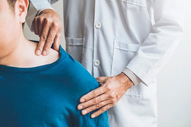 Lichamelijke arts in overleg met de patiënt over schoudermuscule pijnproblemen fysiotherapie diagnoseconcept
