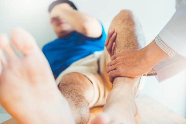 Lichamelijke arts overleg met patiënt knieproblemen fysiotherapie concept