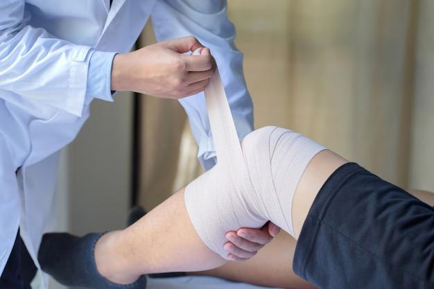 Lichamelijke handen wikkel de knie om de patiënt.