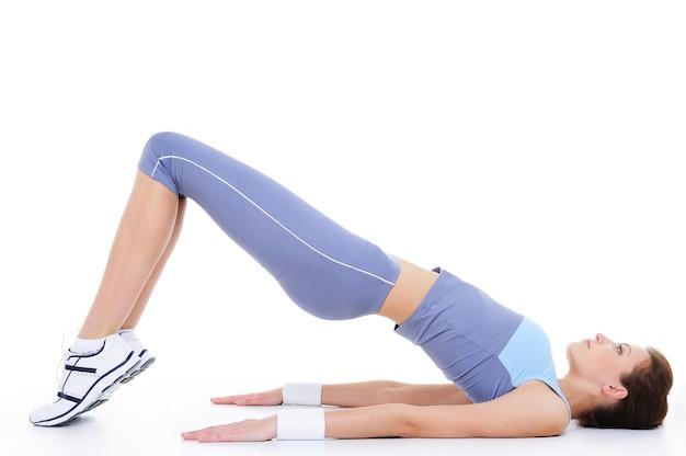 Lichamelijke oefening op de vloer door jonge vrouw die op wit wordt geïsoleerd