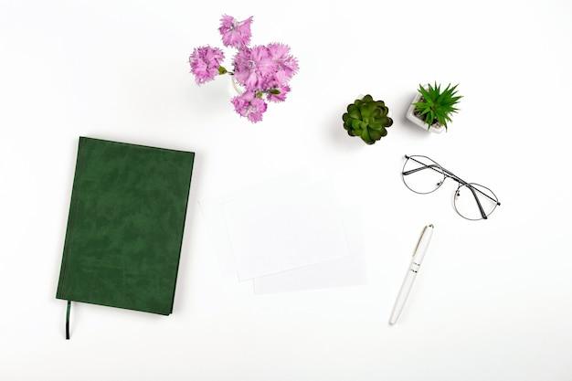 Licht ansichtkaartmodel voor ontwerppresentatie op een witte werkplek met notitieboekjepenglazen en flo...