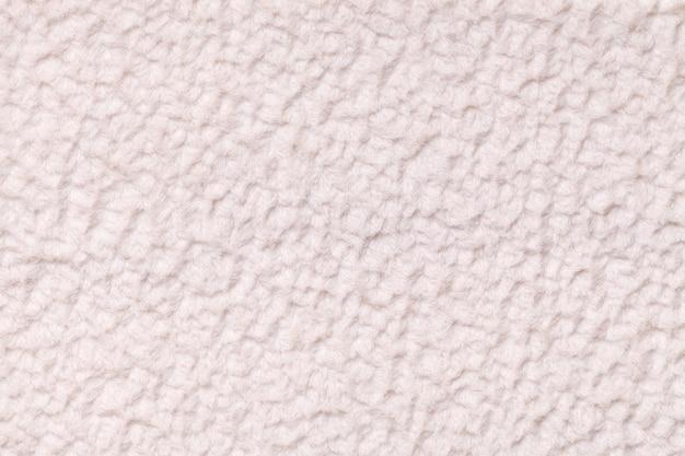 Licht beige pluizige achtergrond van zachte, wolachtige doek, textuur van textiel