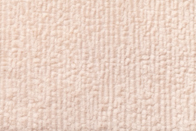 Licht beige pluizige achtergrond van zachte, wollige doek. textuur van textielclose-up.