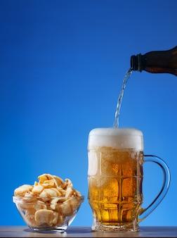 Licht bier dat in mok en snacks in plaat op blauwe achtergrond wordt gegoten