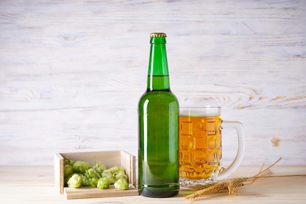 Licht bier en hopbellen op een houten ruimte.