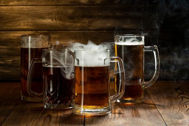 Licht bier met schuim in mokken met rook in een bar op een houten tafel