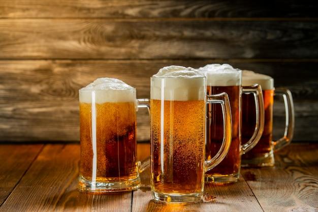 Licht bier met schuim in mokken op een houten tafel