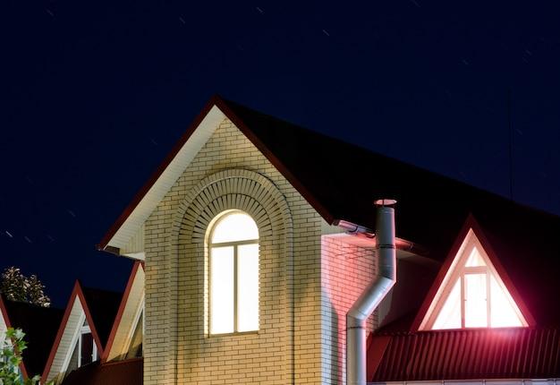 Licht bij het nachtelijk gebogen raam op de bovenste verdieping, het roze licht van de driehoekige ramen