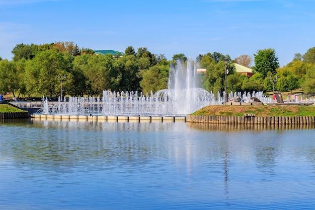 Licht en muziek fontein op het horseshoe-eiland in tsaritsyno-park in moskou tegen de midden-tsaritsynsky-vijver op zonnige zomerochtend