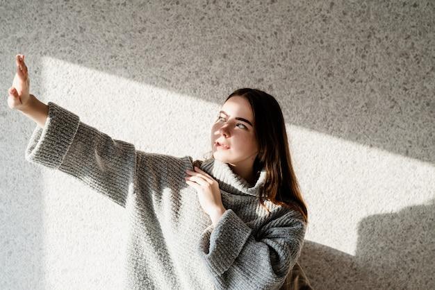 Licht- en schaduwportret. mooie jonge vrouw met een schaduwpatroon op het gezicht. hard licht. licht en schaduwen