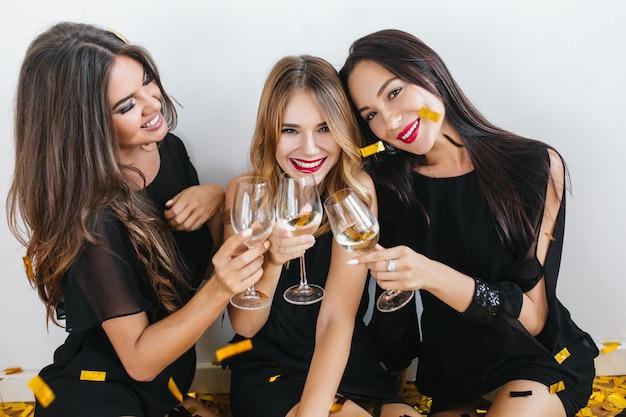 Licht gebruinde blonde vrouw met verlegen glimlach poseren tussen haar zussen, verjaardag vieren met confetti op voorgrond