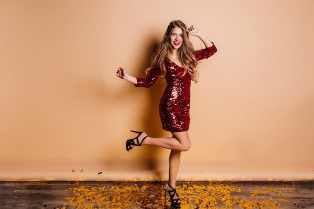 Licht gebruinde dame in zwarte elegante sandalen grappig dansen en lachen op nieuwjaarsfeest