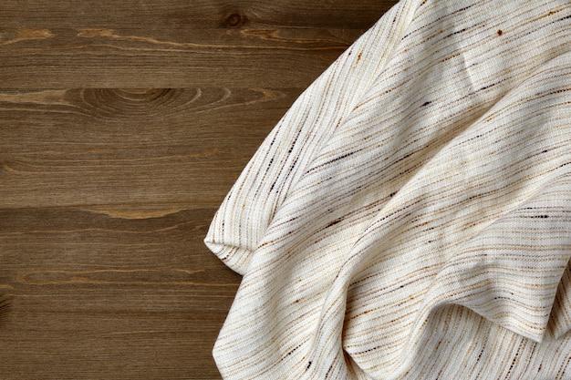 Licht grof linnen tafelkleed op een donkere houten tafel