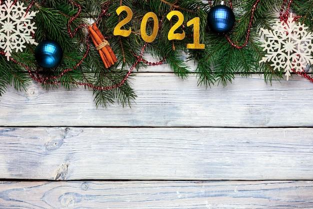 Licht houten kerst achtergrond met belettering blauwe kerstballen spar takken witte sneeuwvlokken...