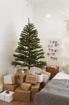 Licht interieur van een slaapkamer versierd met een kerstboom met slingers en geschenken