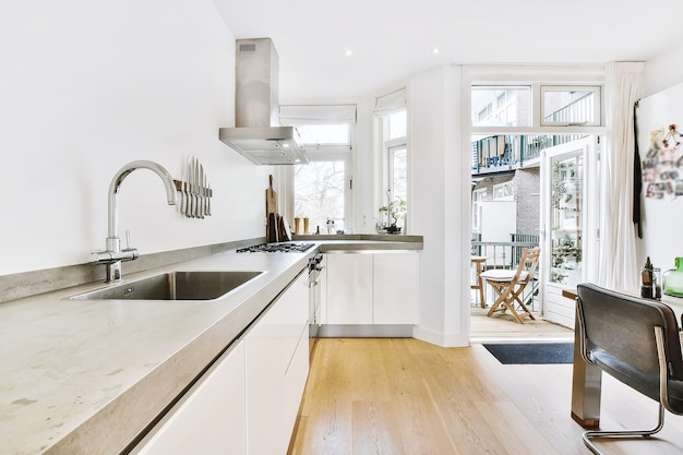 Licht interieur van keuken met grijze toonbank en open deur die leidt naar gezellig balkon van flatgebouw