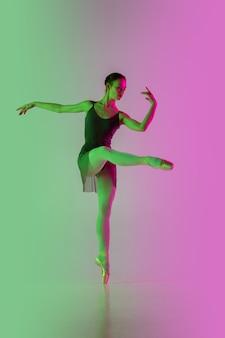 Licht. jonge en gracieuze balletdanser die op roze-groene muur met gradiënt in neon wordt geïsoleerd. kunst, beweging, actie, flexibiliteit, inspiratieconcept. flexibele ballerina, gewichtloze sprongen.