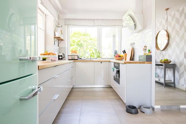 Licht keukeninterieur met vers fruit en twee dierenkommen op de vloer in echte foto met raam