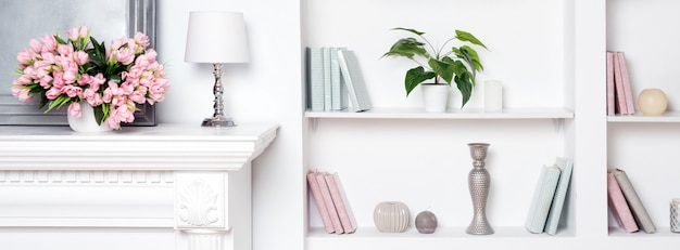 Licht luxe interieur met open haard en bloemen. planken met boeken en decoraties