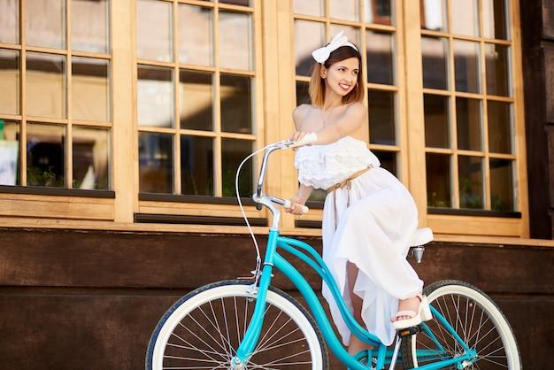 Licht meisje op uitstekende fiets bij muurachtergrond met vensters