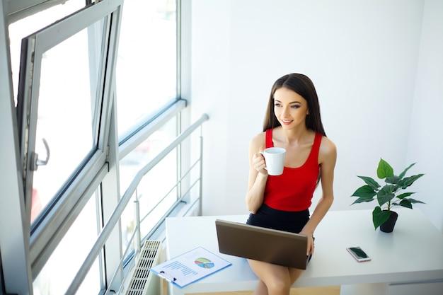 Licht modern kantoor. gekleed in rode trui en zwarte rok.