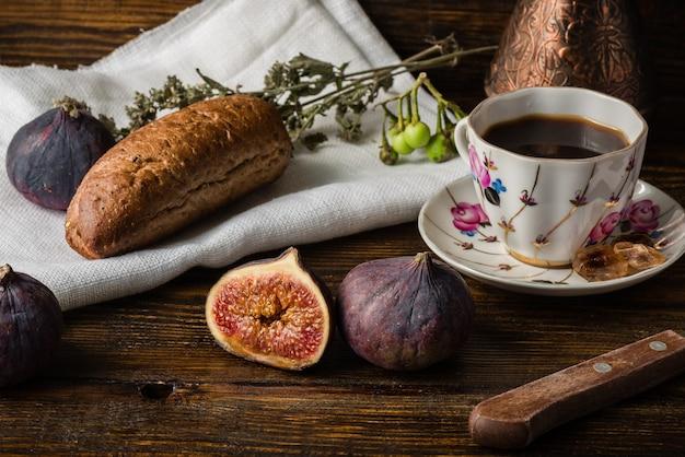 Licht ontbijt met koffie, broodje en enkele vijgen.