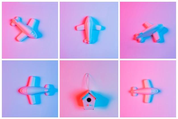 Licht op vogelhuis dat met miniatuurvliegtuig tegen roze achtergrond wordt omringd