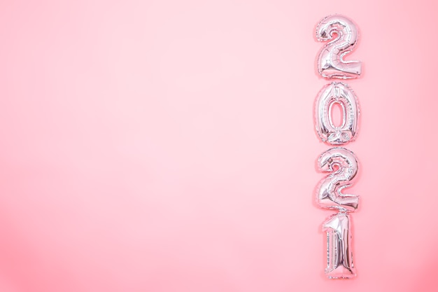 Licht roze achtergrond met zilveren nieuwjaarsballons in de vorm van getallen aan de rechterkant, nieuwjaarsconcept